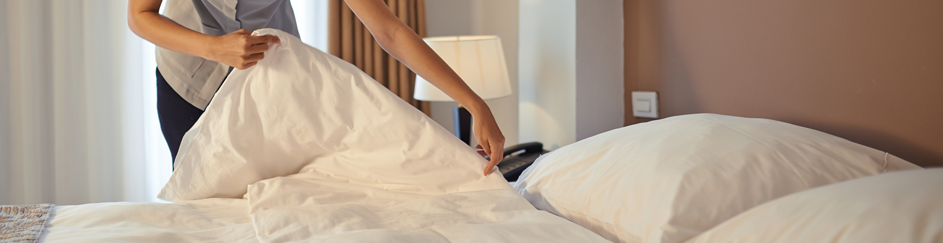 A hotel worker making a bed with fresh linens.