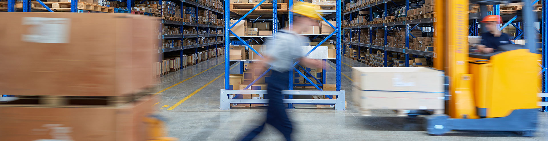 A worker on foot and a worker in a forklift pass each other in a warehouse full of cardboard boxes.