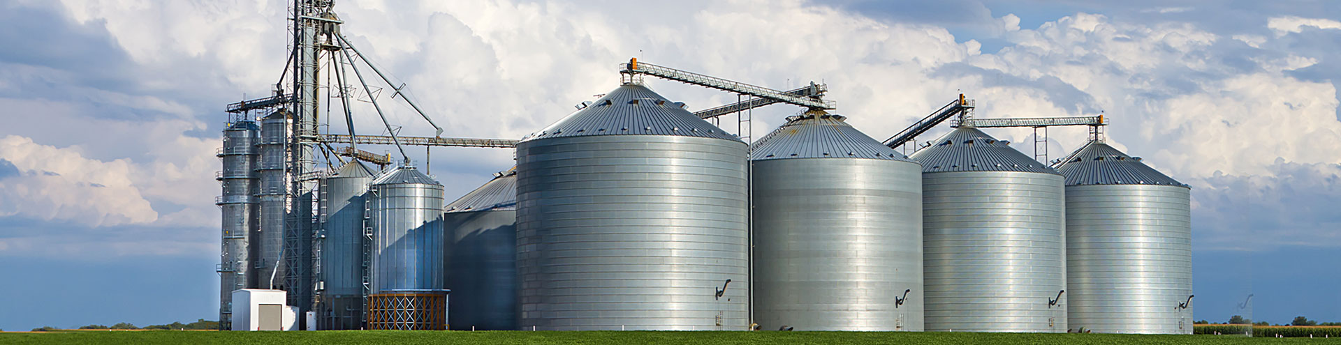 A large collection of metal silos sitting on a farm with clouds in the background.