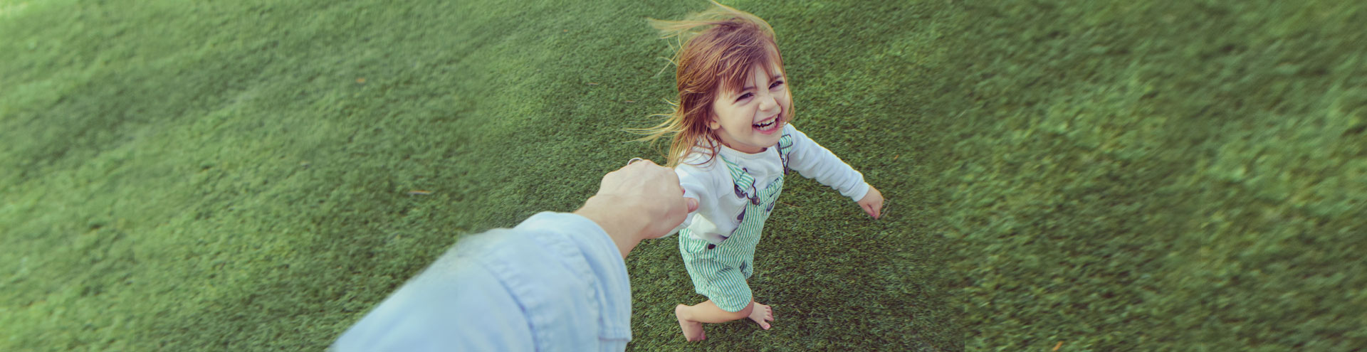 A little girl running in the grass holding her parents hand.