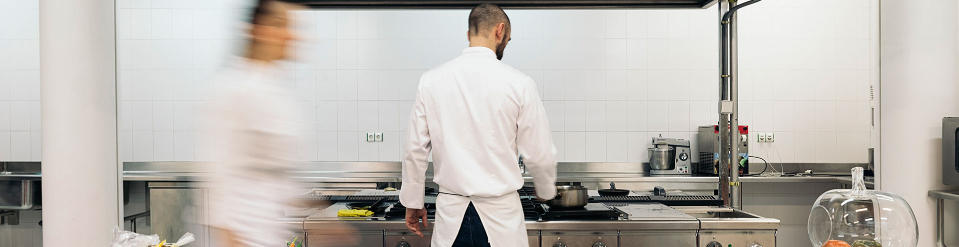 A chef with his back turned towards the camera cooking on a stove in front of while another chef passes behind.